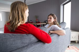 Positive female friends meeting at home to chat. Two women resting on couch in living room and talking. Friendship concept